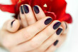 Closeup cupped hands with dark manicure and red flowers