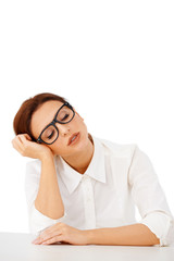 Bored businesswoman sleeping at her desk