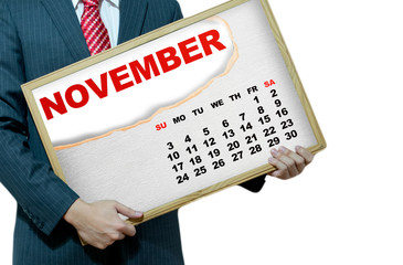 Business man holding black board - calendar 2013