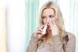 Erkältete Frau benützt Meerwasser Nasenspray