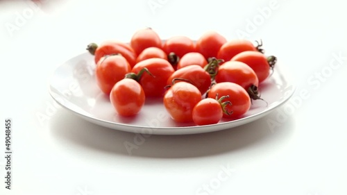 Woman takes tomatoes on a plate