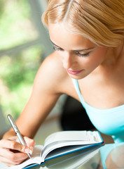Young woman studying with notebook, indoors