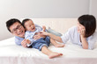 happy family playing on white bed