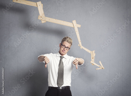 Upset businessman in front of descending graph.