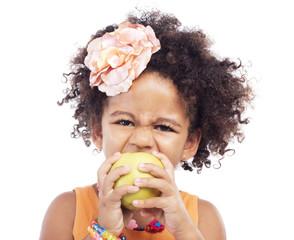 Funny little girl biting an apple