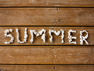 Summer text engraved with stones