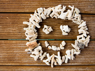 Smiling face made of pebbles over wooden plank