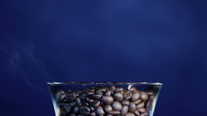 Grains of the roasted coffee in a glass  with a smoke