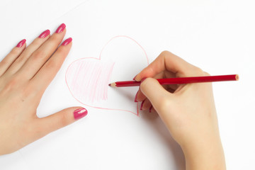 hands painting a heart with a pencil