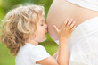Child kissing belly of pregnant woman