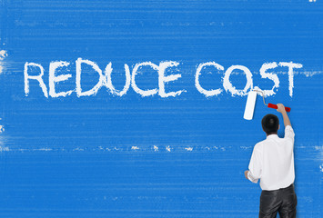 Man painting word on cement texture wall background, Cost reduct