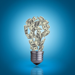 light bulb with money banknotes inside it on blue background