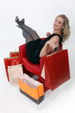 Woman relaxing surrounded by shopping bags