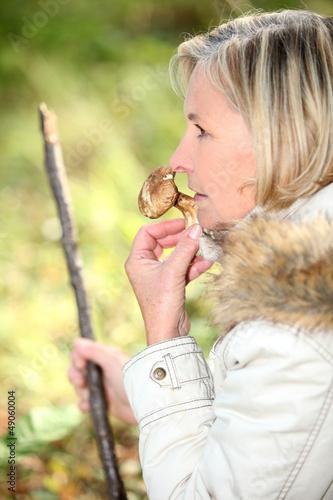 Blond woman smelling mushroom