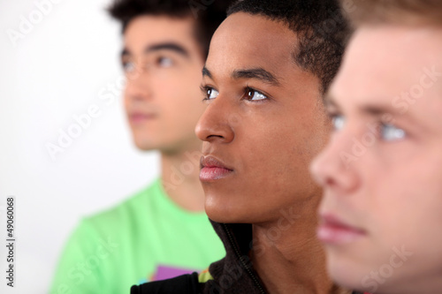 trio of male friends in profile looking in same direction