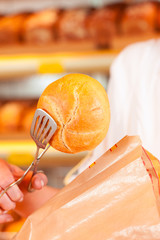 Salesperson is packing bread in bakery