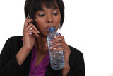 Woman with mobile phone drinking water