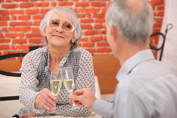 older couple toasting at restaurant