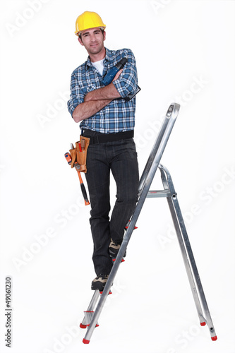 Tradesman standing on the steps of a stepladder