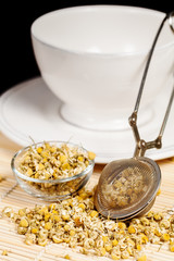 Dry chamomile with tea strainer and glass dish