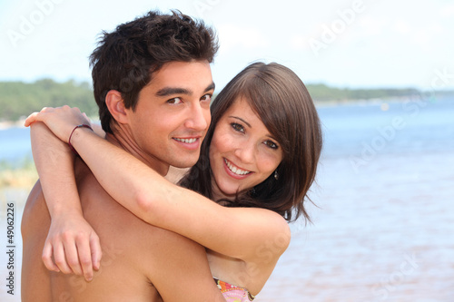 Teens embracing on the beach