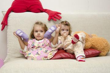 Две маленькие девочки сидят на диване