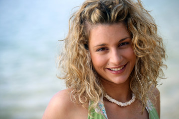 Cute curly-haired blond stood by the ocean