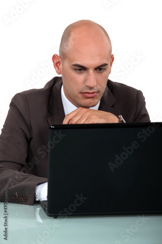 Bald office worker sat at computer