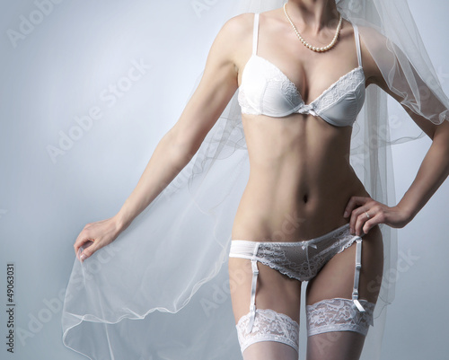 Sexy body of a young bride in white erotic lingerie on grey