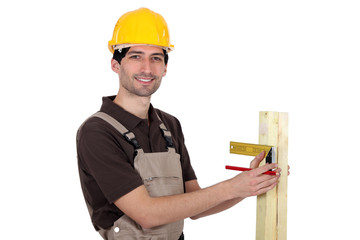 portrait of young carpenter taking measurements