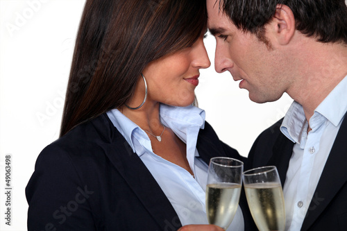 Flirtatious business couple drinking champagne