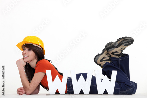 Female builder laying by large WWW letters