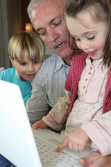 grandfather and grandchildren with laptop