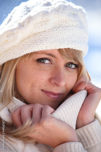 Blonde woman in a cream jumper and hat
