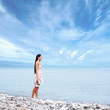 A young woman on a blue sky and sea background