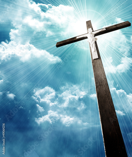 cross in sunrays against cloudy sky