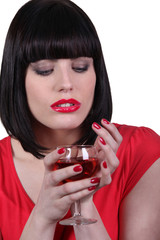 a brunette woman looking a wine glass