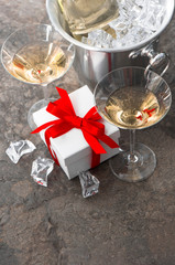 two glasses, bottle of champagne and gift box