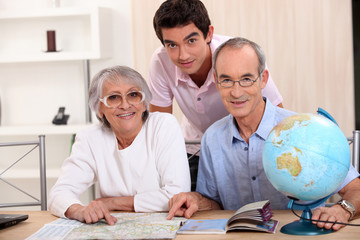 Young man and senior couple seeking a route on a map