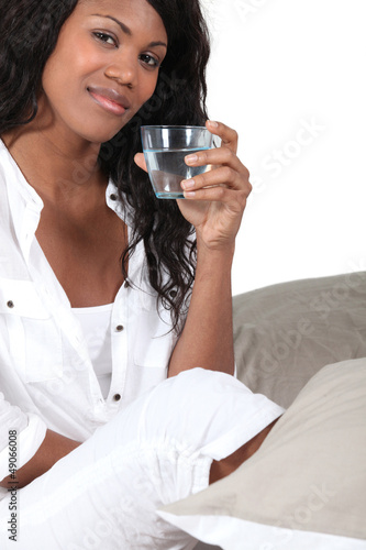 Woman drinking a glass of water in bed