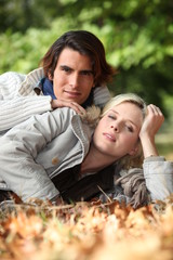 Young couple laying in autumnal leaves