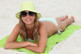 Young girl lying on a lime green towel on the beach