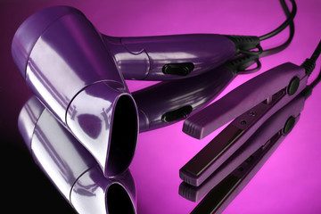 Hair dryer and straighteners  on purple background