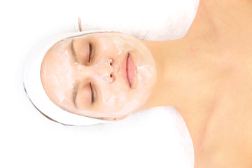 Young woman with creamy facial mask