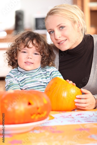 Woman carving pumpkins with her child