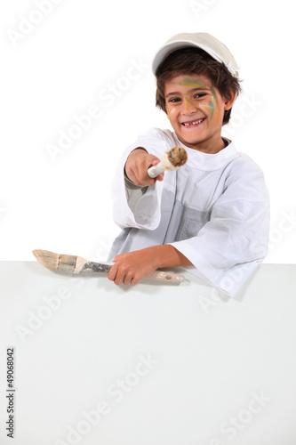 schoolboy wearing overalls enjoying painting
