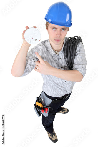 An electrician holding a fire alarm.
