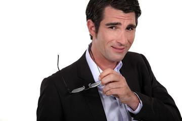 confident businessman holding his eyeglasses