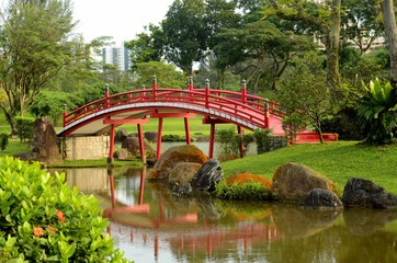 Curved red bridge over stream in Japanese Gardens, Singapore.