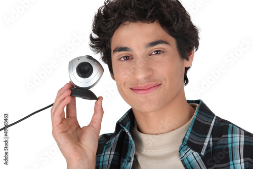 Young man holding a webcam